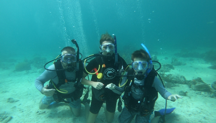 Andy and his family take an underwater pic SCUBA diving