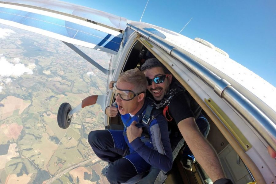 A tandem instructor smiles with his student before exiting the plane.