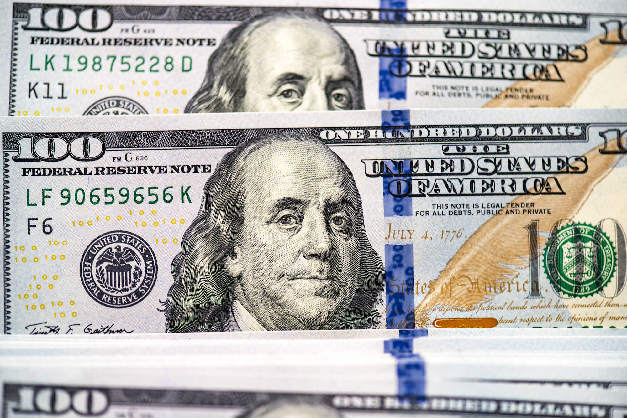 An image of multiple one hundred dollar bills in US Currency